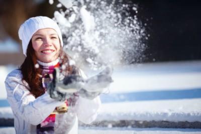 Jeune femme qui lance de la neige