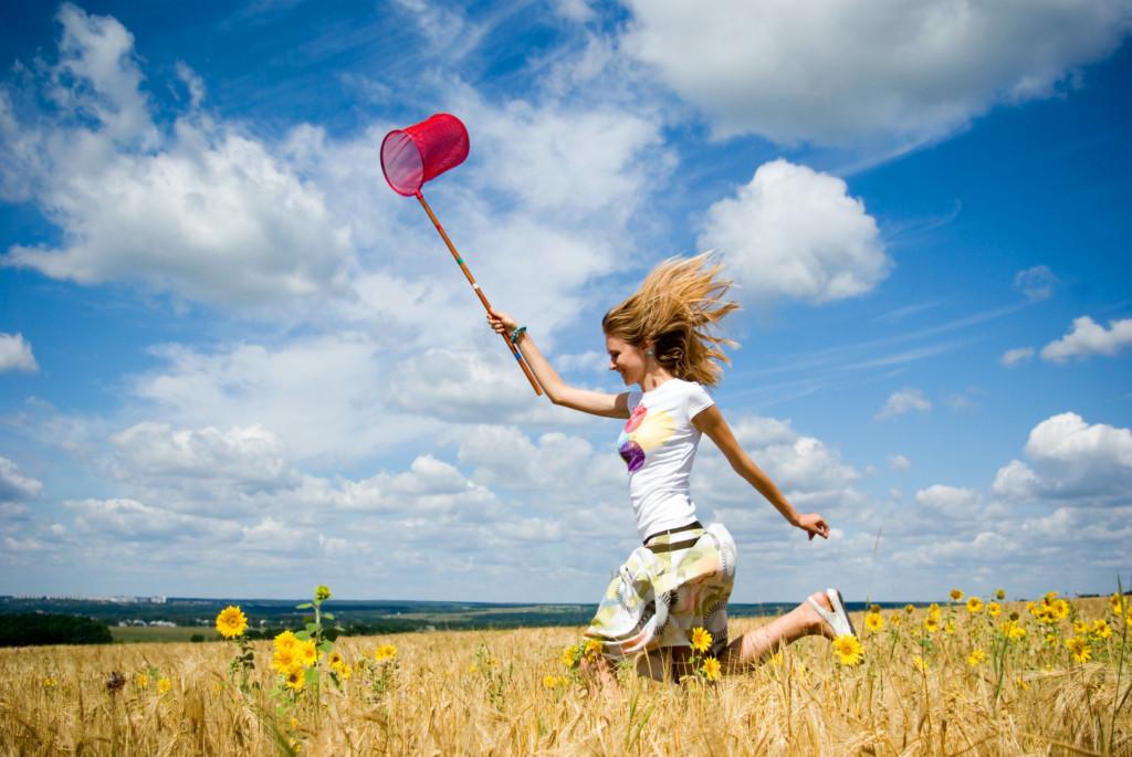 Belle jeune femme qui coure dans un champ de blé
