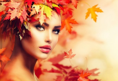 Jolie femme avec des feuilles en automne
