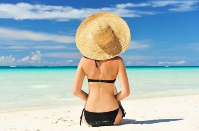 Jolie femme de dos avec un chapeau sur une plage