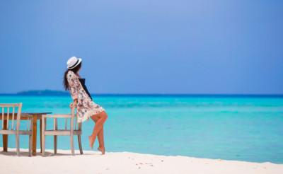 Belle jeune femme avec un chapeau au bord d'une plage