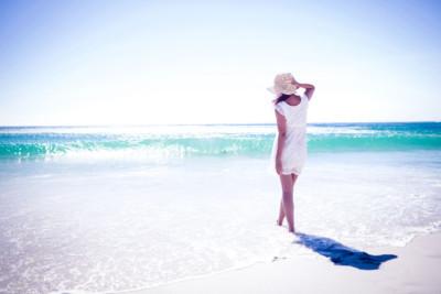 Belle jeune femme avec un chapeau au bord de la mer