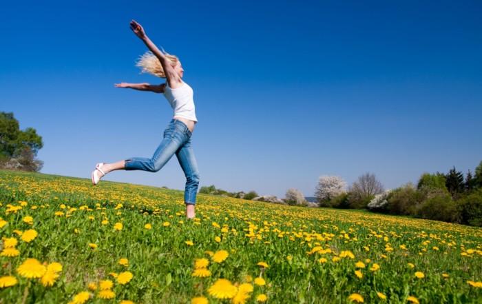 Jeune femme qui coure dans une prairie fleurie