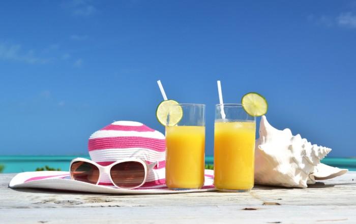 Jus d'orange, chapeau et lunettes de soleil sur une plage tropicale