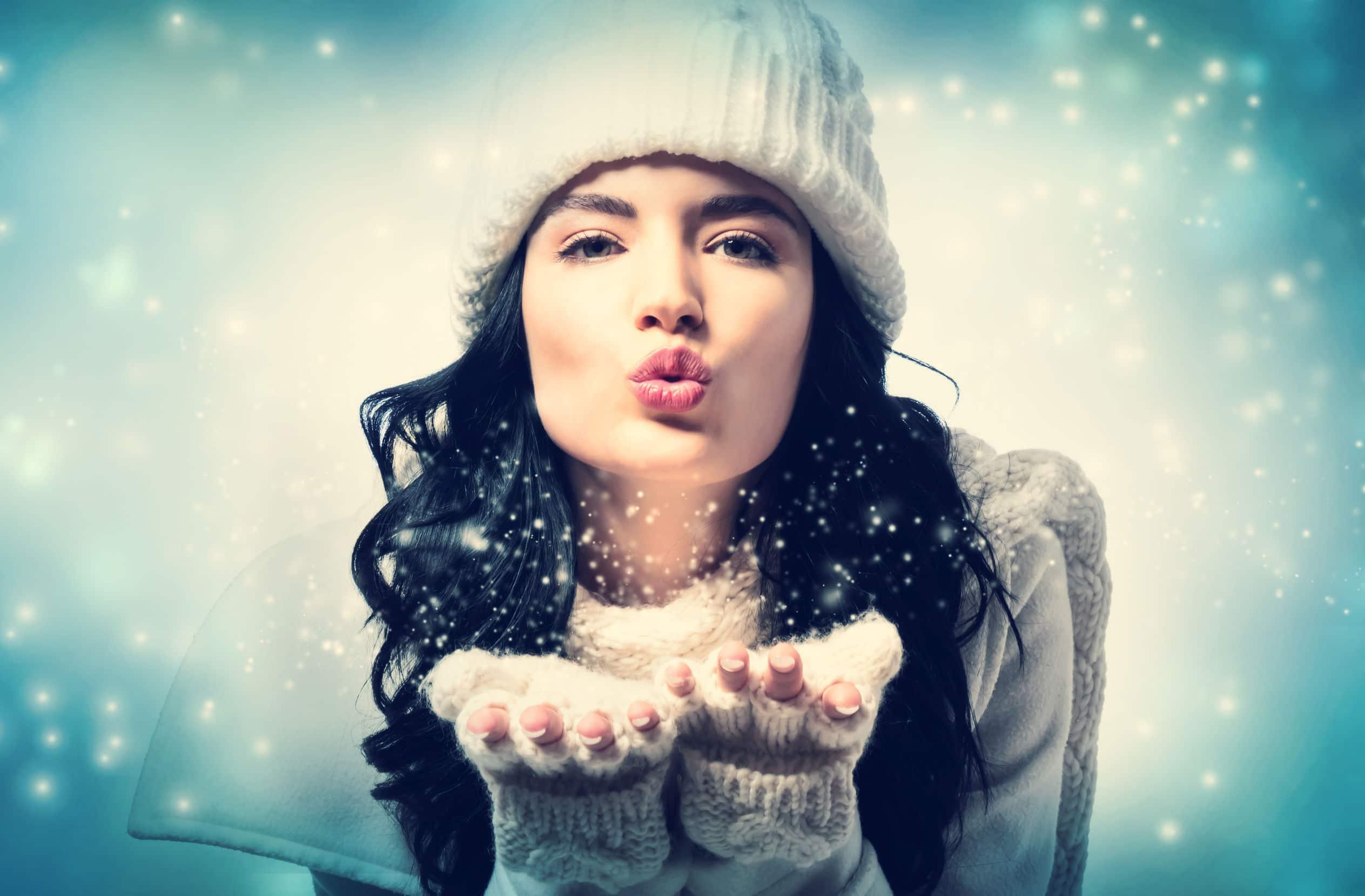 Jeune et jolie jeune femme qui envoie un bisou en habit d'hiver